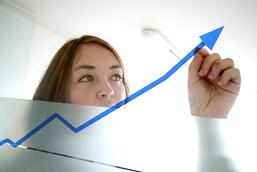 business woman drawing a graph on a glass window in an office - focus is on graph